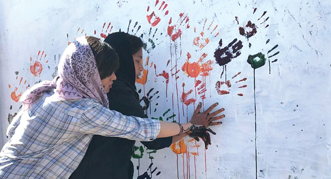 Two students place painted hands on wall
