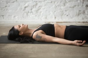 Mujer ejercitando respiración en pilates
