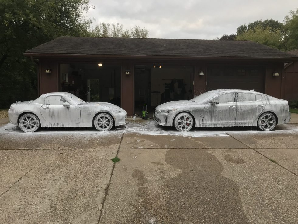 A 2016 Mazda MX-5 Miata ND and a 2019 Kia Stinger covered in snow foam from Griot's Garage in a driveway in front of a brown garage.