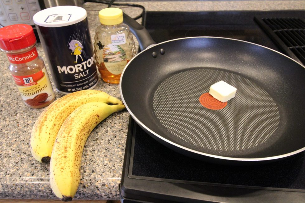 Frying pan with butter on the stove, with banans, salt, cinnamon, and honey on the kitchen counter.