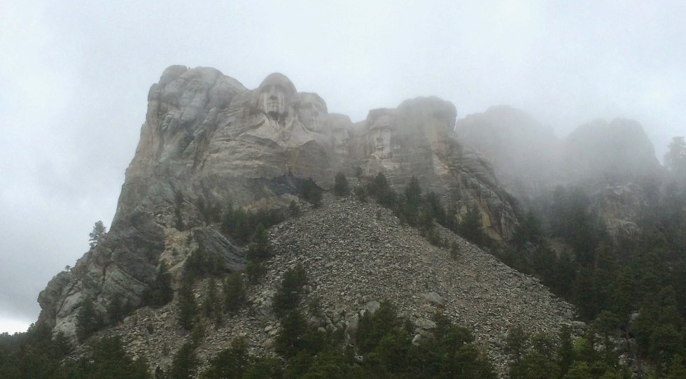 Mount Rushmore National Memorial shown through fog on overcast day