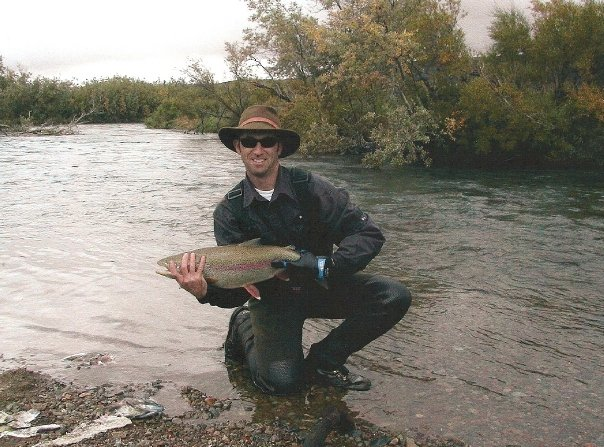 Fly fisherman holding a very large trout