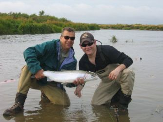 A fly fishing guide in Alaska holding a big trout for a client