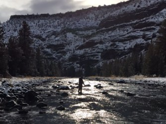 A man fly fishing in winter on a high desert river