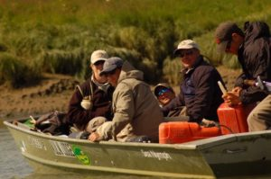 A boat in Alaska with fly fishermen and their guide. The guide is filling the engine with gas.