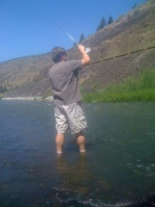 A fly fisherman starting a roll cast on a run on the Crooked River on a summer day