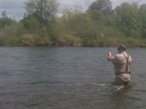 A fly fisherman standing in a deep large river.