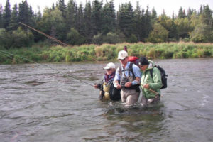 A fly fishing guide helping to clients wade back to the boat