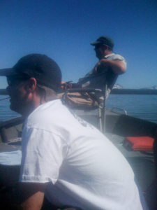 Two men fly fishing from a boat