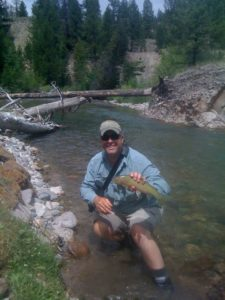 Fly fisherman holding a nice cutthroat trout from an Idaho stream