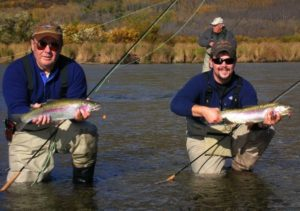 Two men holding large rainbows with a fly fisherman behind them fighting a fish