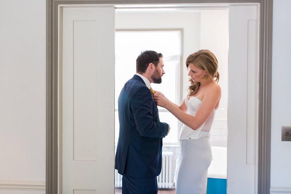 bride helping tie groom's tie