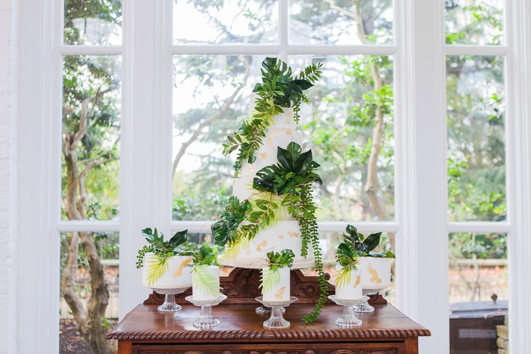 wedding cake with tropical foliage troprical wedding inspiration shoot trend