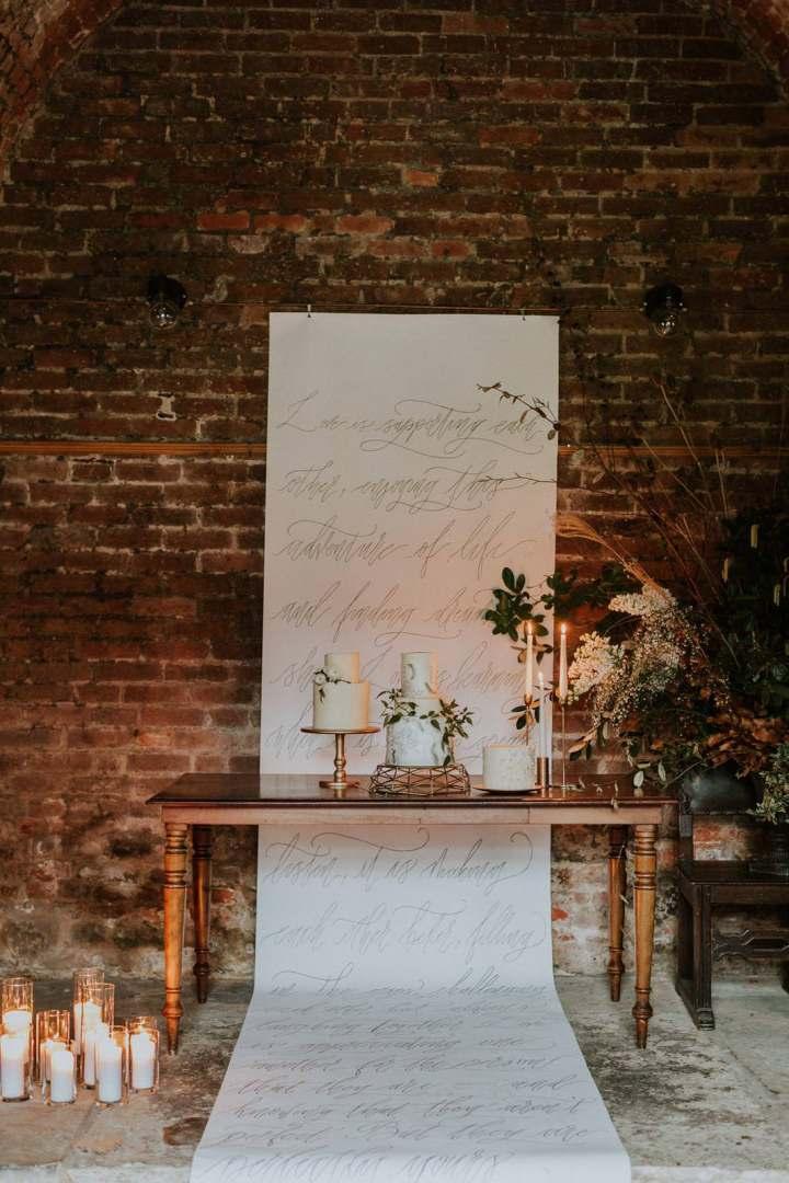 trio of buttercream cakes with calligrahpy backdropat london wedding venue the Charterhouse