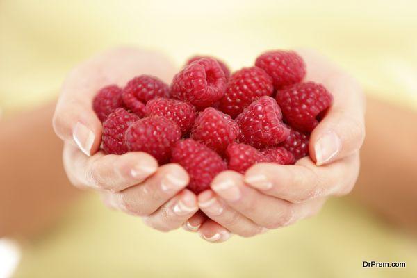 Raspberries. Woman showing raspberries in closeup. Healthy food and raspberry concept.