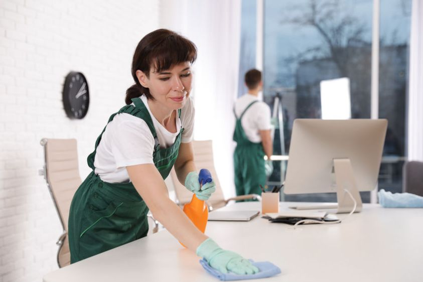 Professional janitor cleaning table in modern office
