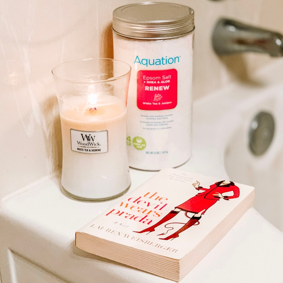 5 Simple Steps For An At Home Spa Night - Walmart Aquation Epsom Salt Renew White Tea and Juniper, and WoodWick White Tea and Jasmine Candle with The Devil Wears Prada Book on a bath tub