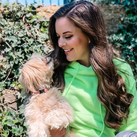 Girl with long brown hair, neon sweatshirt, and puppy