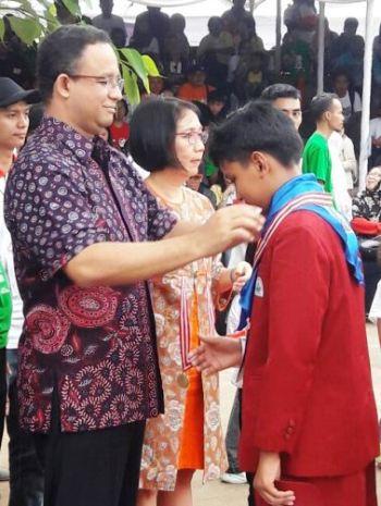 Siswa SD Unggulan AL-YA'LU Dies Haditsa Putra Nursadih menerima pengalungan medali emas Olimpiade Sains Kuark level III dari Mendikbud Prof. Anies Rasyid Baswedan, Ph.D.
