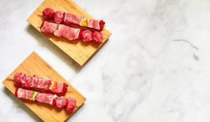 raw beef skewers on wooden board