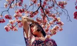 brunette woman looking sad while surrounded by pink blossoms