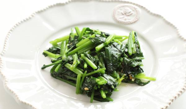 water spinach cooked served on white plate with ketcap manis