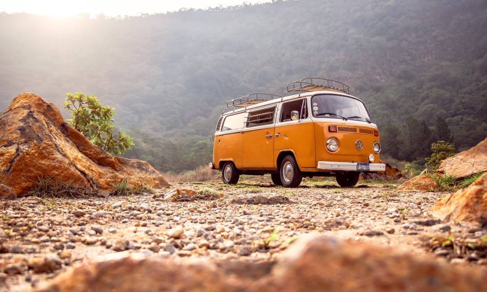orange kombi van in rugged terrain