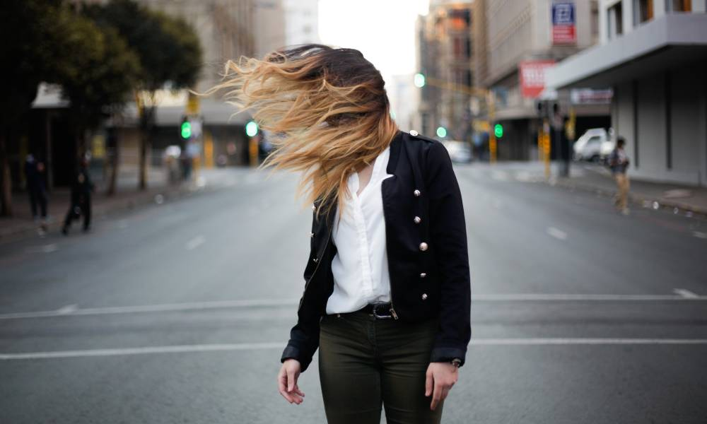 woman freelancer stading in street with hair over her eyes