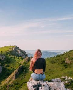 young woman pink hair sitting on a hill looking at the view