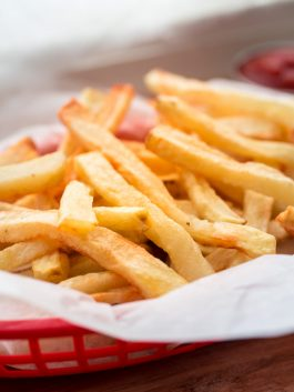 french fries in red woven basket with ketchup
