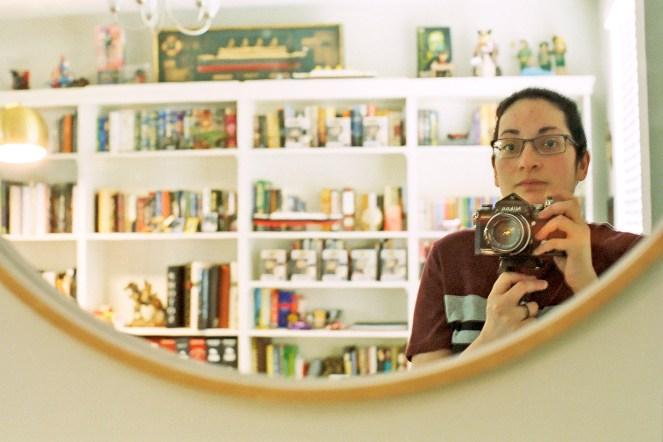 woman in mirror with Nikon F film camera