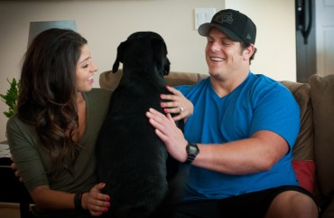"J.R. and Gissell Sweezy pet their dog, Otis, at their home in Bellevue. ""I want J.R. to live his dream,"" said Gissell. ""We just want happiness, a big family and lots of dogs."""