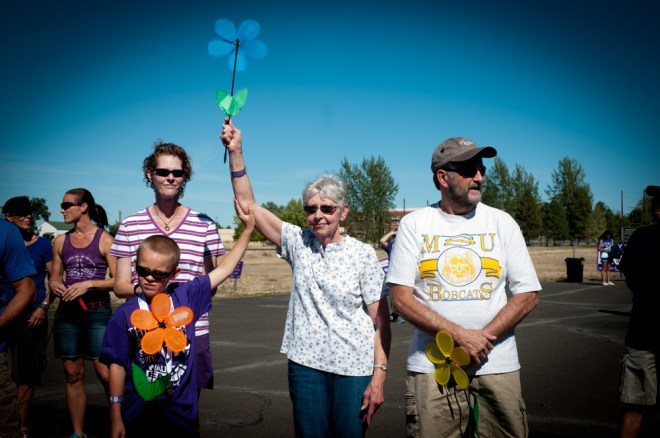 A young boy helps his grandmother raise her blue flower during the opening ceremony of the Walk to End Alzheimer's.