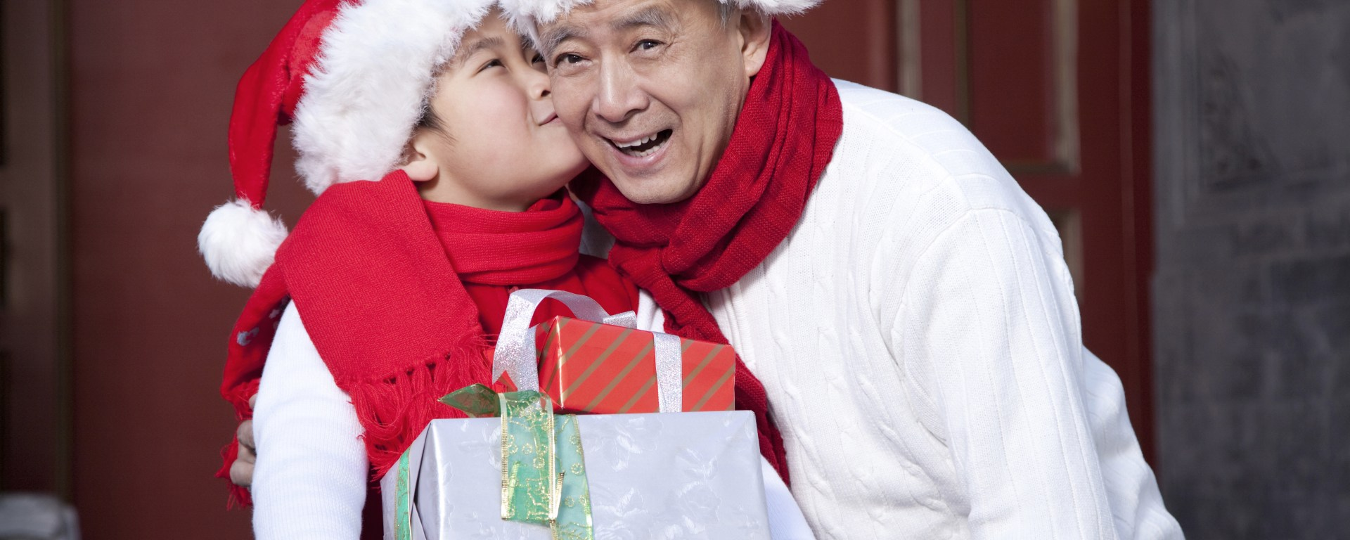 A Grandpa and grandson holding Christmas Gifts
