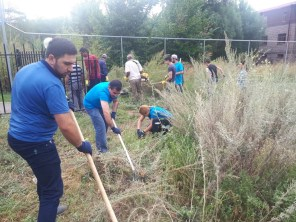 The backyard of the AMAA Center in Gyumri getting cleared of weeds