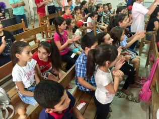 As VBS children perform on stage in Artashat, their friends follow along, awaiting their turn (12 Aug. 2018)