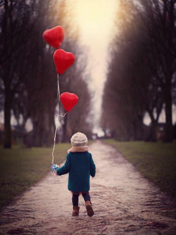 menininho na estrada segurando balões em forma de corações
