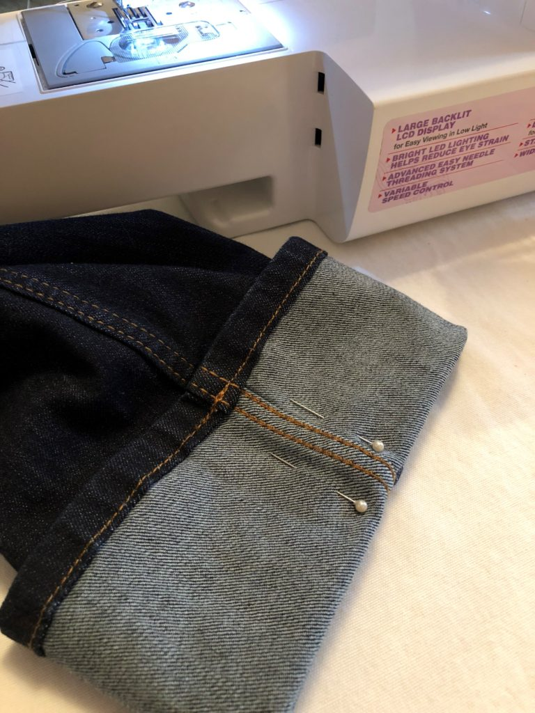 A pair of jeans lays on a sewing table with the bottom part of the pant leg folded up with two pins pinned on each side of the side seam. How to hem jeans.