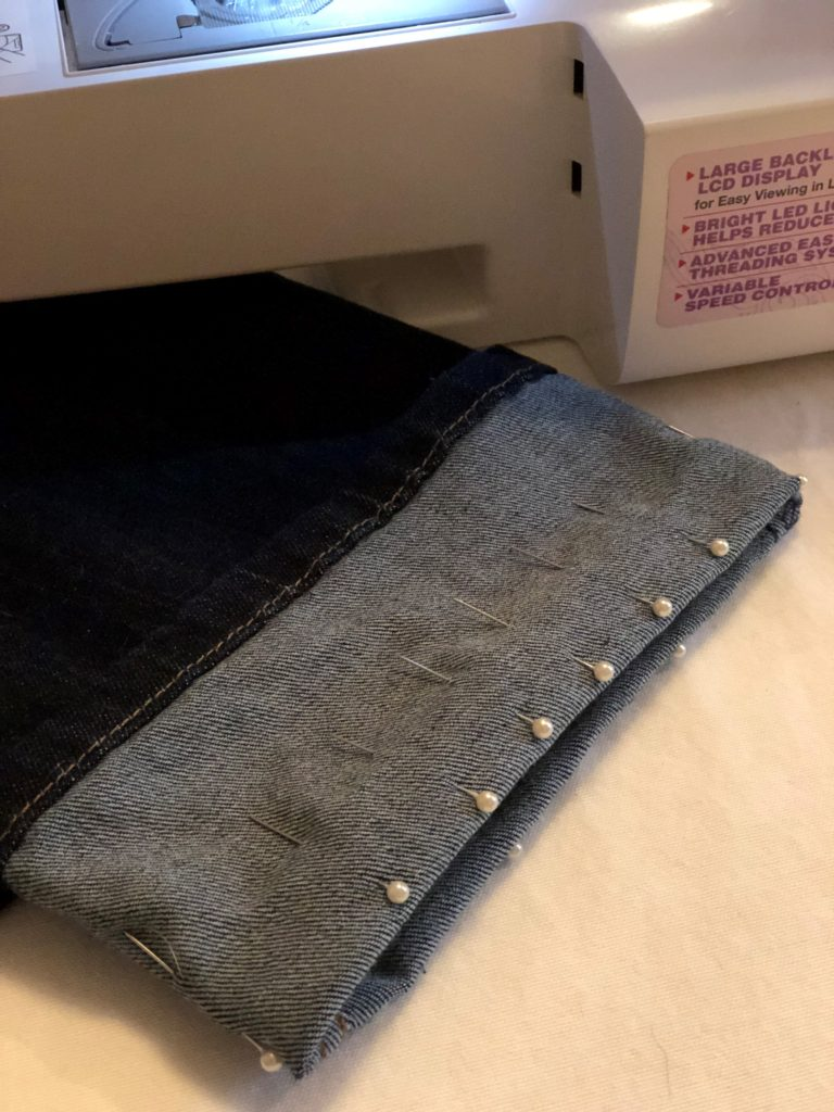 A pair of jeans lays on a sewing table with the bottom part of the pant leg folded up with pins spaced about one inch apart all the way around the pant leg to hold hem in place while sewing. How to hem jeans.