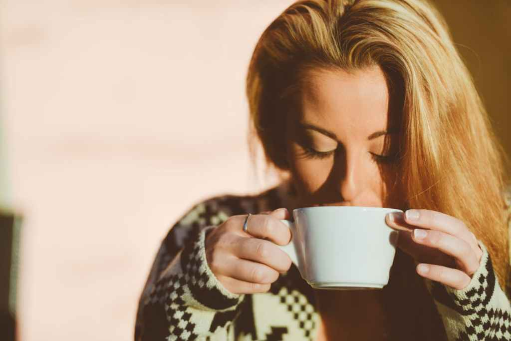 A blond woman with her hair down, looking down into the cup of coffee she is sipping, holding onto it with both hands.