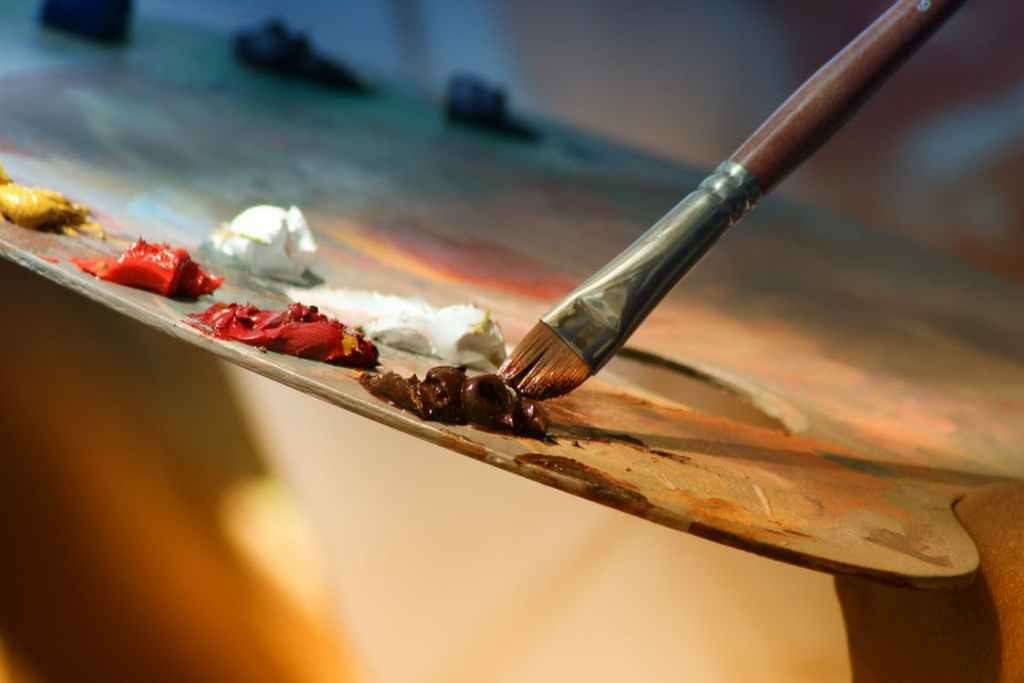 A paintbrush touches a wooden painter's palette , with white, yellow, red and orange paint on it.