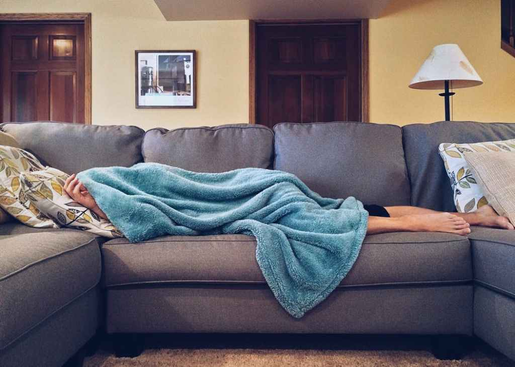 A woman naps on the couch midday because her baby won't sleep at night.