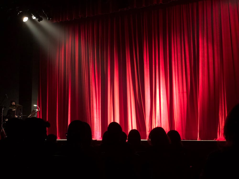 Stage lights shine on the stage with the curtain drawn with an audience anticipating the show.