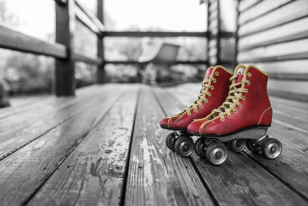 Red roller skates with yellow laces sit on a wooden deck.