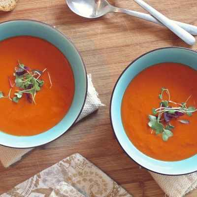 Two bowls, turquoise in color sit on a wooden table filled with tomato soup. Instant pot recipes.