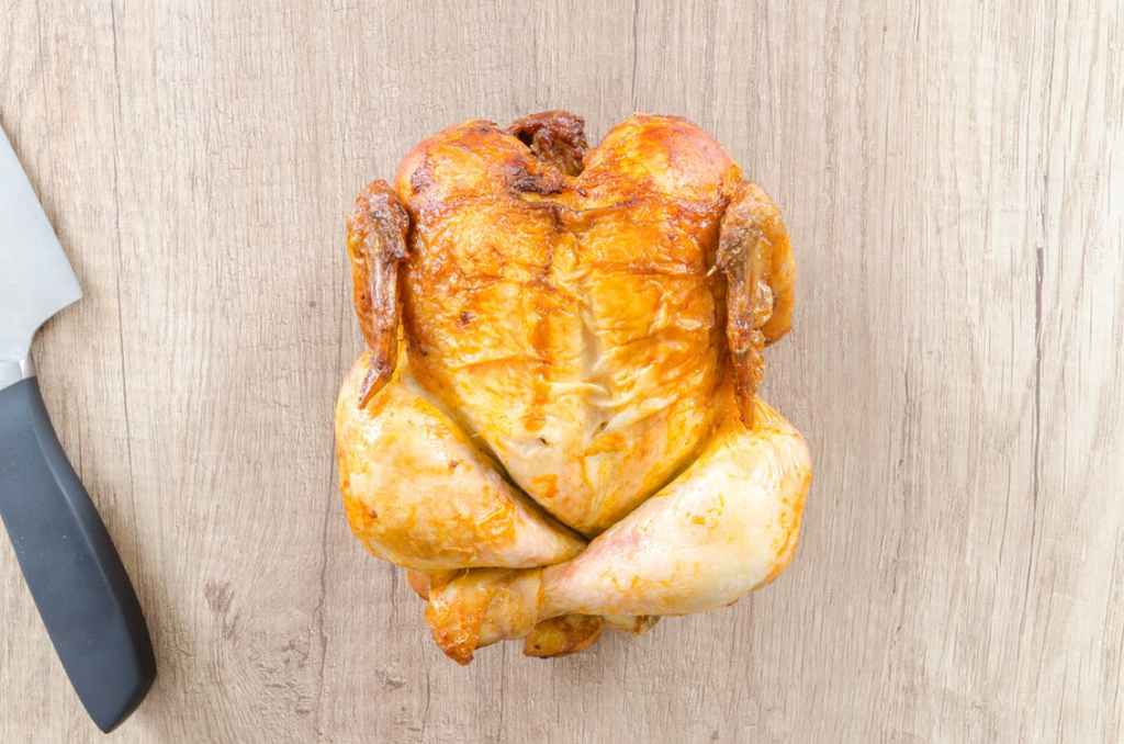 A cooked, whole chicken lays on a cutting board next to a knife. Instant pot recipes.