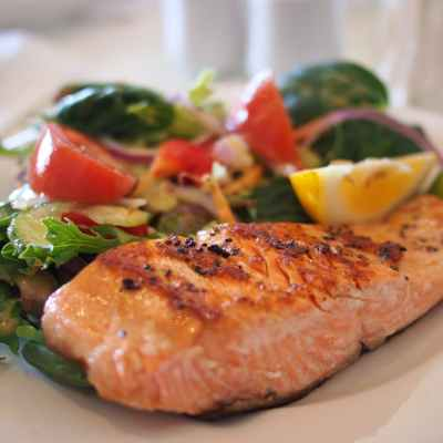 Grilled salmon on a plate next to a tossed salad with a lemon wedge.