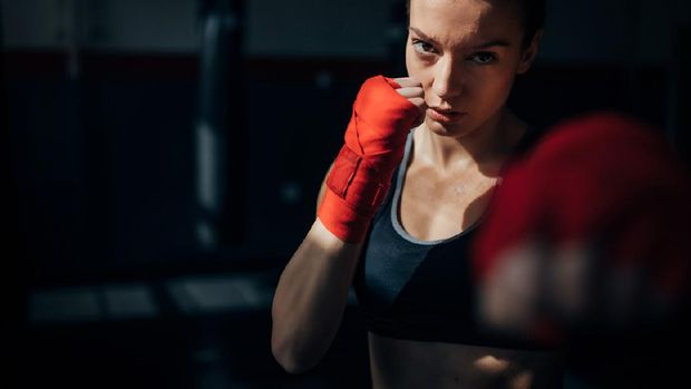 Photo of a fit female muay thai fighter training with a punching bag in a boxing hall. She is jumping on a boxing ring in an underground fight club, training kicking.