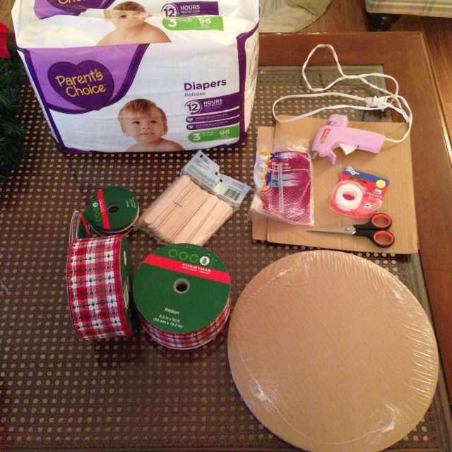 Materials needed: Diapers, thick ribbon, thin ribbon, cardboard cutouts (I used cake plates), hot glue gun, scissors, tape, and a not pictures box cutter