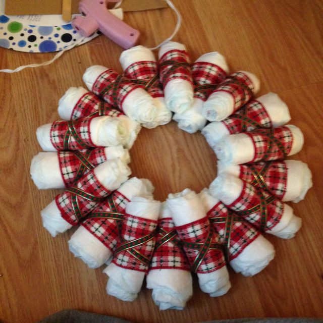 So I rolled a bunch of tighter diapers to fill in the blank spaces. I did not secure them in place - I used the smaller ribbon to do so. Here's how:  hot glue the end of the ribbon strand to the back of the cardboard. Then weave it over and around each diaper until you've gone around the entire donut. Then secure a new strand of ribbon to the back and weave/wrap it around each donut again - just in the opposite direction to achieve the X.